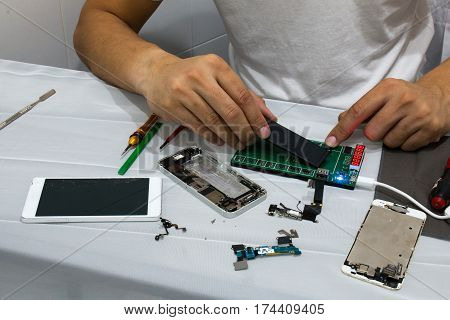 Mobile repair technicians are checking batteries to customers at his shop. Mobile phone battery could be damaged.