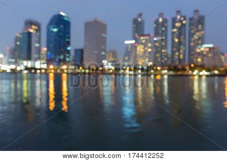 Twilight blurred bokeh city office building with reflection abstract background