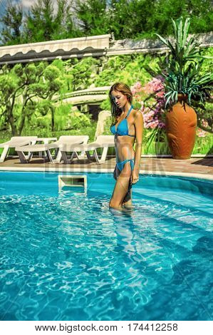 Beautiful slim sexy woman wearing blue bikini stay in outdoor water pool on resort