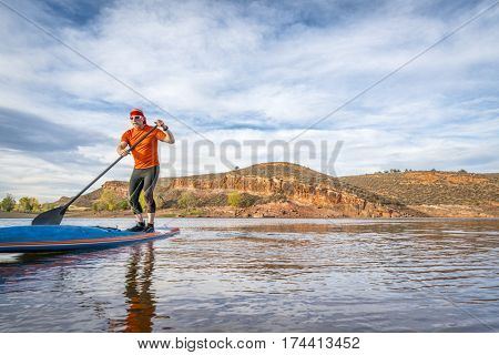 A senior male paddling on a stand up paddleboard on a calm mountain lake - Horsetooth Reservoir near Fort Collins, Colorado, fall scenery
