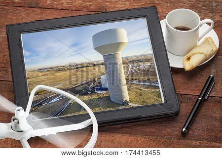 aerial photography concept - reviewing aerial pictures of a water tower on  a digital tablet with a drone rotor and coffee, screen picture copyright by the photographer