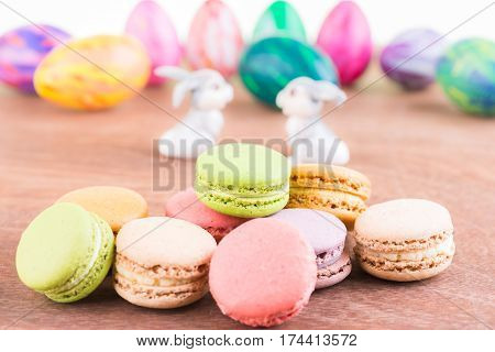 Macaroos with Easter egg and bunnies on wooden table