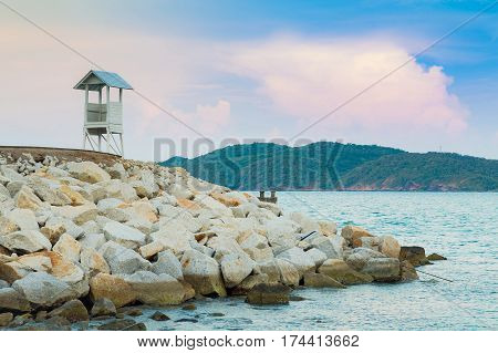 Lifeguard over rock bearer seacoast skyline natural coastline background