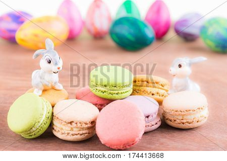 Macarons and bunnies with Easter eggs at the background