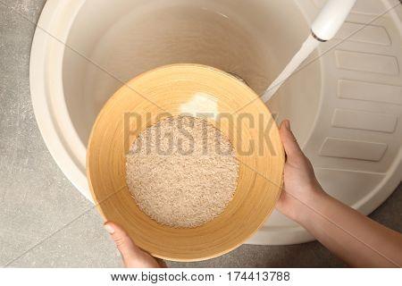Woman rinsing rice in bowl