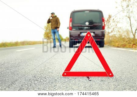 Traffic warning sign on road with car and driver talking on phone on background