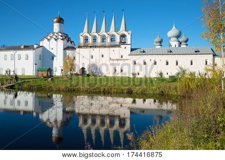 October day in the monastery pond. View of the bell tower of the Tikhvin Assumption monastery. Russia