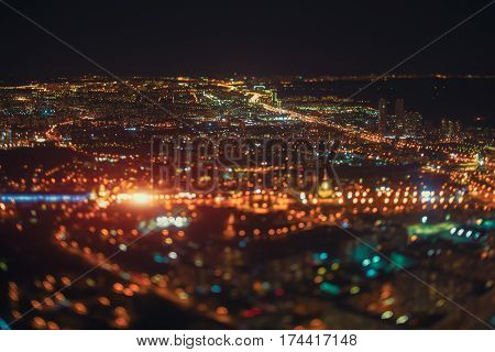 True tilt shift shooting of highway in night metropolis from very high point: multiple residential houses road in focus going to horizon strong bokeh and flare in foreground multiple warm lights