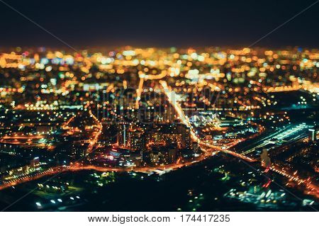 True tilt shift shooting of highway and railway station during night in metropolis from high above: multiple residential houses road intersection in focus in foreground strong bokeh in background
