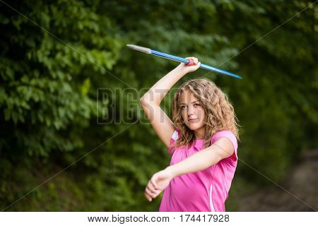Young woman practicing throwing a javelin - close up view