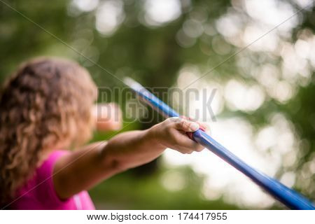 Young woman practicing throwing a javelin in a close up from rear view with focus to her hand gripping the shaft