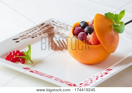 Fruit ice. Fruit dessert with many fruits. Orange strawberry cherry bilberry served on white table with chocolate. Fruits cream. Frozen berries. Top view.