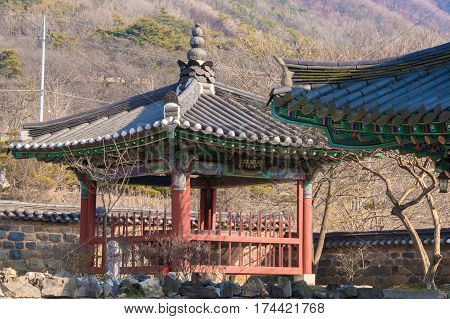 Oriental gazebo with a tiled roof in front of a stone wall at a woodland Buddhist temple in a woodland area in South Korea.