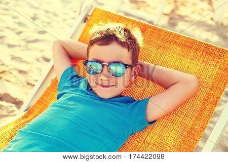 Little boy relax on deckchair at beach vintage