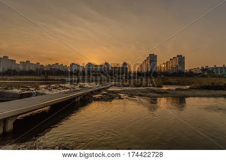 Sunset at a river in South Korea with apartment buildings in the background