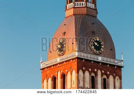 Close Up Of Clock On Tower Of Riga Dome Cathedral In Riga, Latvia. Sunny Blue Sky Background. Tower In Golden Hour At Sunset Or Sunrise Time