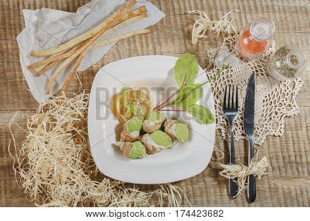 Boiled cockles with tasty sauce. Boiled fresh cockles on lettuce vegetable for seafood serving. Fresh cockles scald with seafood sauce on brown cloth background, select focus.
