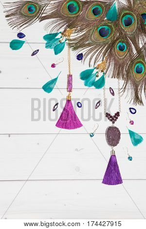 Handmade turquoise and violet bijouterie with gems, tassels and peacock feathers in boho style, lying flat on the white wooden vertical background, top view