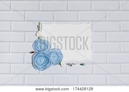 White Paper Background With Handmade Gentle Blue Ranunculus Flowers, Roses and Crystals, Lying Flat on the White Brick Wall, Top View. Have an Empty Rectangular Place For Your Text.