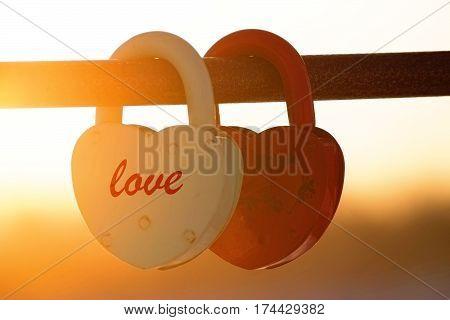 two heart shaped padlocks beautiful sunset sunbeans