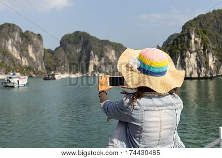 Woman traveler photographing beautiful natural view at Halong bay in Vietnam