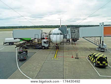 An aircraft is prepared on the apron of an airport for departure. Baggage stands for loading ready, the catering is delivered and a tanker vehicle refueled the aircraft with kerosene.