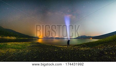 Silhouette of a man with a flashlight observing beautiful wide blue night sky with stars and visible Milky way galaxy at lake. Astronomy orientation clear sky concept and background.