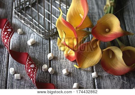 Orange Yellow Calla Lilies With Red Ribbon And White Marshmallows On Wooden Gray Background.