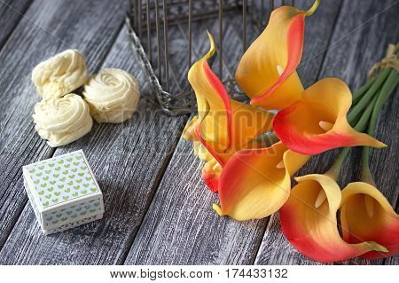 Orange Yellow Calla Lilies Bouquet With Marshmallow And Cardboard Box On A Gray Wooden Background.