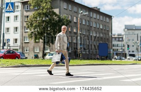 sale, traffic and people concept - senior man with shopping bags walking along city crosswalk
