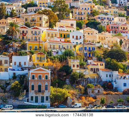 Colorful houses lining harbor at Simi, Greece