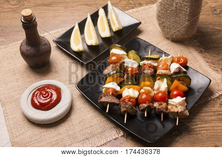tasty skewers with grilled meat soft cheese and vegetables served on a dark plate