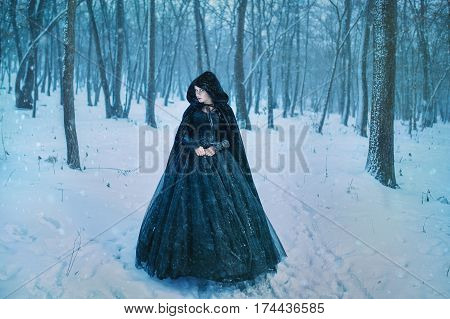 Mysterious woman in black dress walking in winter forest