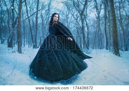 Mysterious woman in black dress walking in winter forest