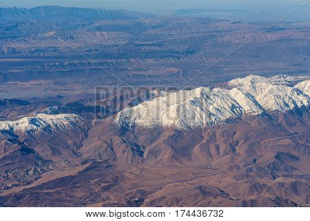 Scenic aerial view of lifeless mountains with snowy tops