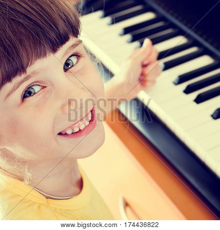 Toned Photo of Happy Small Girl with the Piano Keyboard