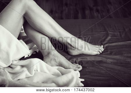 Beautiful female legs on a bed. Black-and-white photo