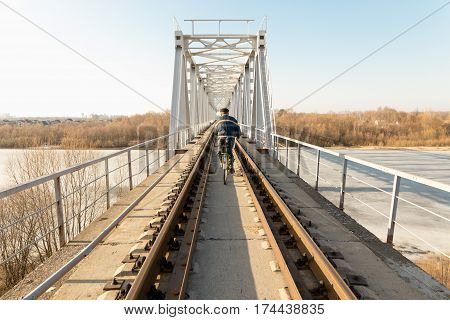 A Man Riding A Bike On The Train In The Spring Into The Distance.