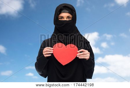 love, charity, valentines day and people concept - muslim woman in hijab holding red heart over blue sky and clouds background