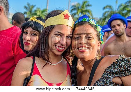 RIO DE JANEIRO, BRAZIL - FEBRUARY 28, 2017: Young women wearing costumes of Wonder Woman and Frida Kahlo with unibrow having fun at Bloco Orquestra Voadora in Flamengo Park, Carnaval 2017