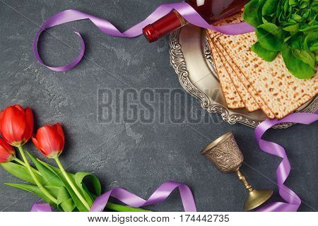 Passover holiday concept matzoh and tulip flowers on dark background. Top view from above