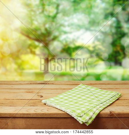 Empty wooden deck table with checked tablecloth over green park bokeh background for product montage display