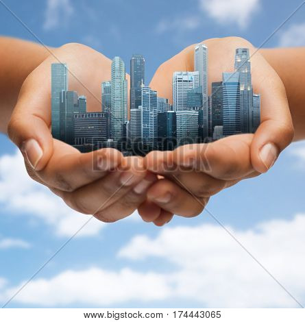 architecture, building, urban and people concept - hands holding city over blue sky background