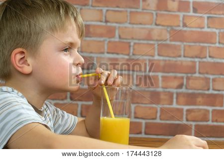 Baby drinking orange juice from glass on the kithen