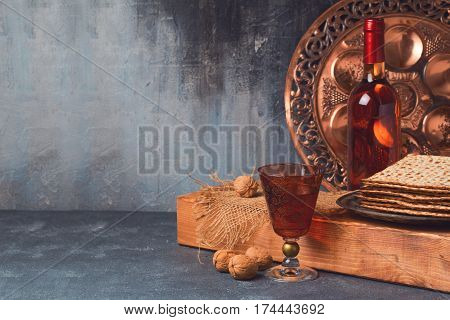 Passover holiday concept with wine matzoh and seder plate over dark background