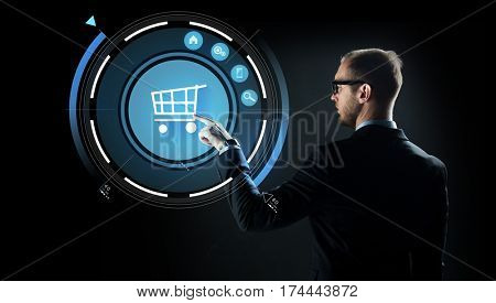 business, e-commerce, future technology, cyberspace and people - businessman in suit and glasses pointing finger to virtual shopping cart projection over black background