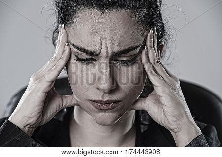 close up portrait of young attractive business woman working at office in stress suffering intense headache and migraine feeling overworked and overwhelmed in work crisis concept