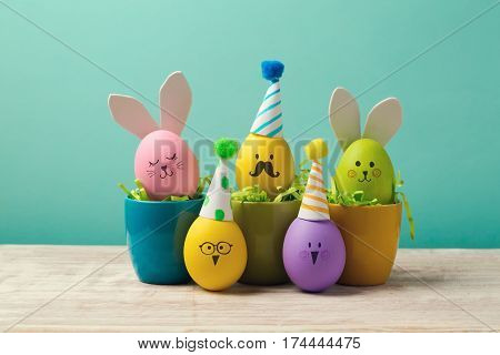 Easter holiday concept with cute handmade eggs in coffee cups bunny chicks and party hats