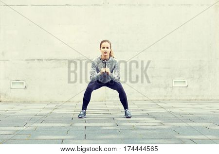 fitness, sport, exercising and healthy lifestyle concept - woman doing squats outdoors