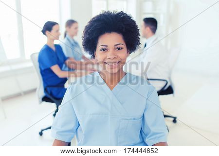 clinic, profession, people and medicine concept - happy african american female doctor or nurse over group of medics meeting at hospital
